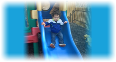 young boy playing slides