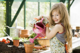 Young girl watering plants in greenhouse smiling