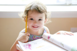 Little toddler girl writing at school desk, homework