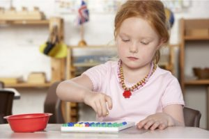 little girl learning and playing in a montessori school
