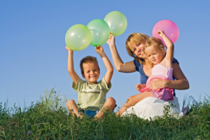 mother and children holding balloons